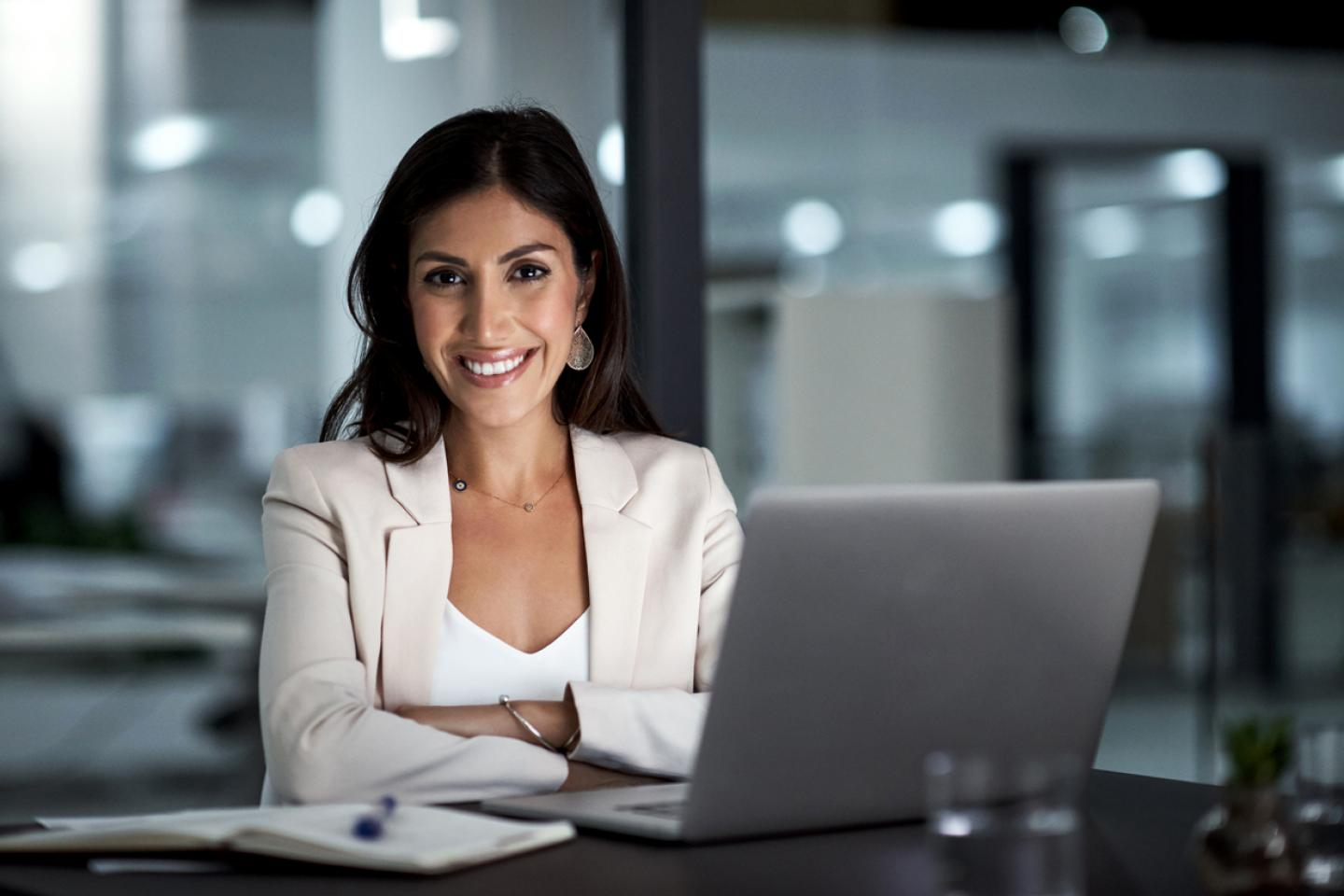 Smiling Business women sitting at desk in front of laptop