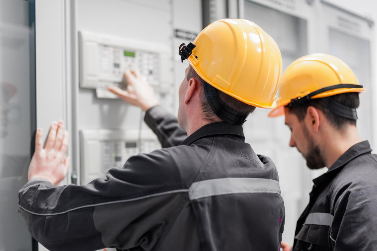 Maintenance workers investigating an electrical panel