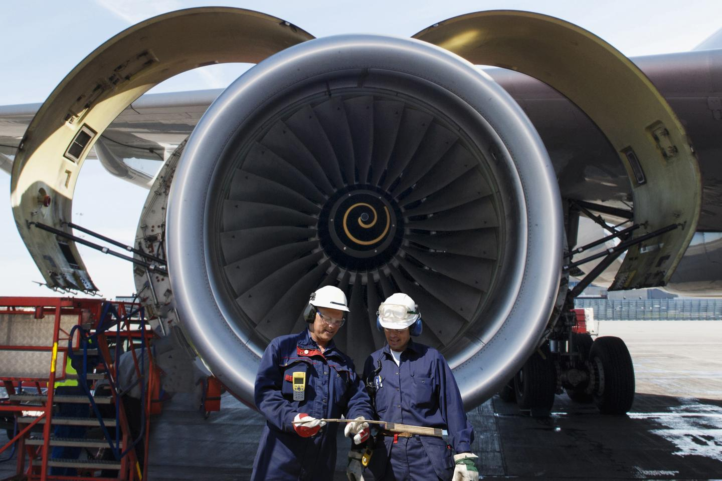 Photo of two men infront of airplane engine